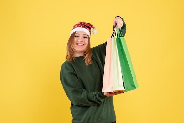 Vooraanzicht jonge vrouw na het winkelen met pakketten