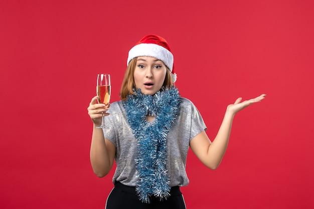 Vooraanzicht jonge vrouw nieuwjaar vieren op de rode muur vakantie kleur kerst