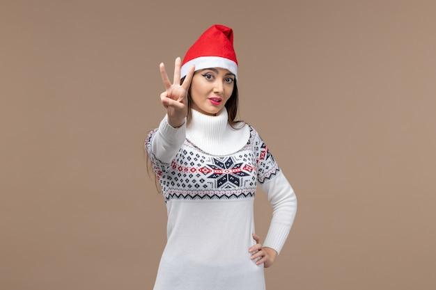 Vooraanzicht jonge vrouw nummer op bruine achtergrond vakantie kerst emotie tonen