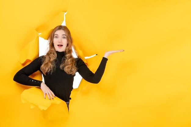 Vooraanzicht jonge vrouw op de gele gescheurde muur