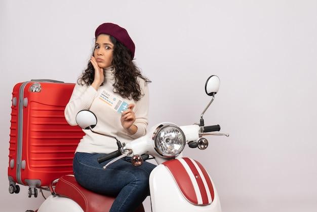 Vooraanzicht jonge vrouw op fiets met ticket op witte achtergrond vlucht kleur motorfiets vakantie weg stad snelheid