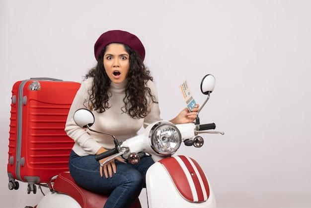 Vooraanzicht jonge vrouw op fiets met ticket op witte achtergrond vlucht kleur motorfiets vakantie wegvoertuig snelheid