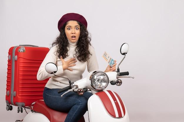 Vooraanzicht jonge vrouw op fiets met ticket op witte achtergrond vlucht weg motorfiets vakantie voertuig stad snelheid kleur
