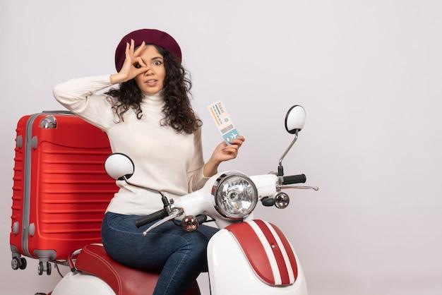 Vooraanzicht jonge vrouw op fiets met ticket op witte achtergrond vlucht weg motorfiets vakantie voertuig stad snelheid kleuren