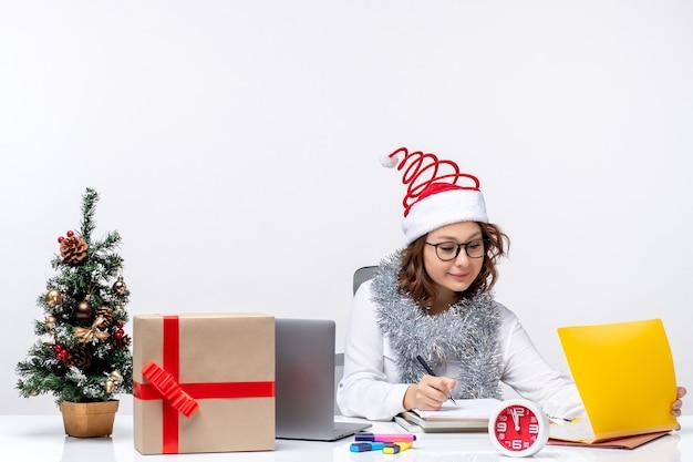 Vooraanzicht jonge vrouw op werkplek schrijven van notities op lichte witte achtergrond