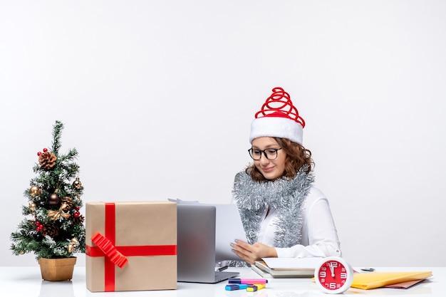 Vooraanzicht jonge vrouw op werkplek werken met documenten op witte achtergrond