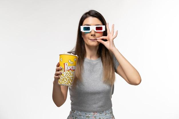 Vooraanzicht jonge vrouw popcorn eten en kijken naar film in d zonnebril op het licht witte oppervlak