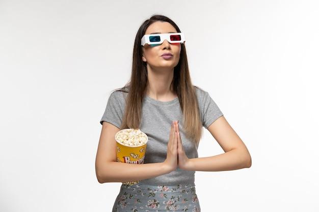 Vooraanzicht jonge vrouw popcorn eten en kijken naar film in d zonnebril op wit bureau