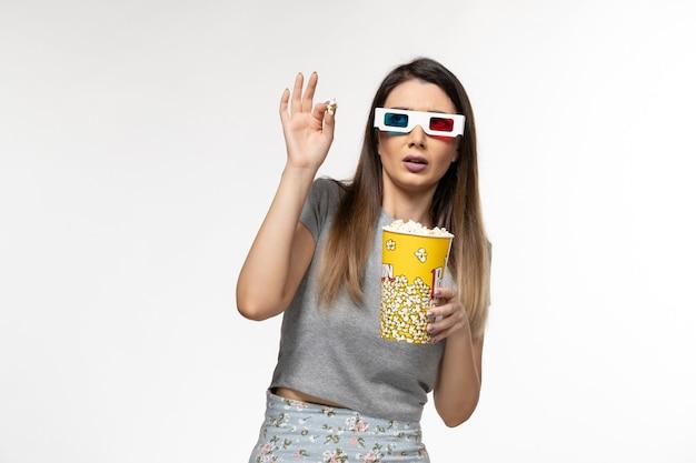Vooraanzicht jonge vrouw popcorn eten en kijken naar film in d zonnebril op witte ondergrond