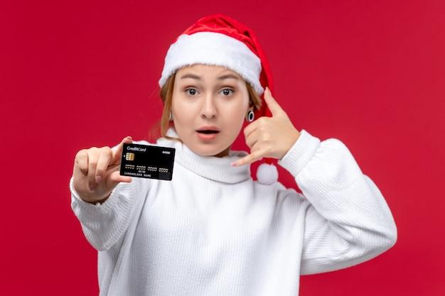 Vooraanzicht jonge vrouw poseren met bankkaart op de rode achtergrond