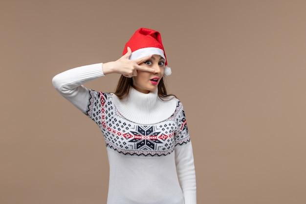 Vooraanzicht jonge vrouw poseren op bruine achtergrond emotie kerst nieuwjaar