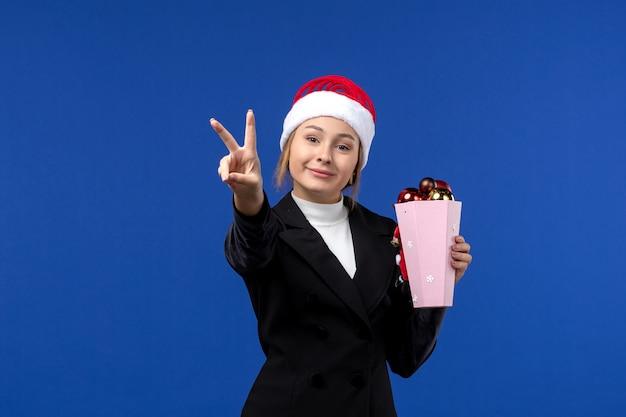 Vooraanzicht jonge vrouw tellen nummer op blauwe muur emotie nieuwe jaar vakantie