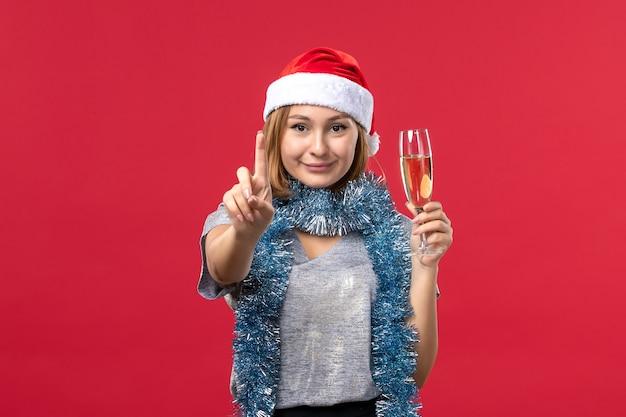 Vooraanzicht jonge vrouw tellen nummer op rode muur kleur kerstvakantie