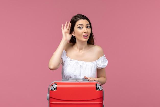 Vooraanzicht jonge vrouw vakantie voorbereiden en luisteren op roze achtergrond in het buitenland zeereis reis reis reis