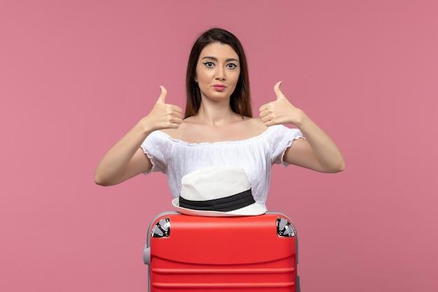 Vooraanzicht jonge vrouw vakantie voorbereiden en poseren op roze achtergrond reis reis in het buitenland zeereis