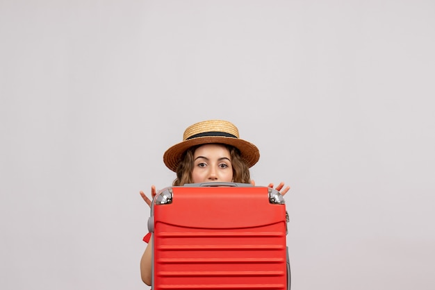 Vooraanzicht jonge vrouw verstopt achter haar valise