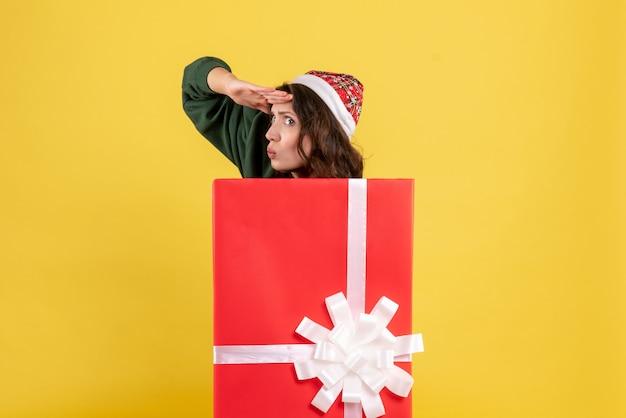Vooraanzicht jonge vrouw verstopt in doos op geel