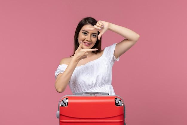 Vooraanzicht jonge vrouw voorbereiding op vakantie en gelukkig gevoel op roze achtergrond in het buitenland zeereis reis reis reis