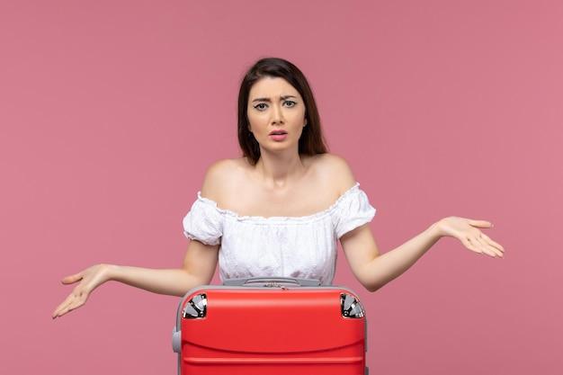 Vooraanzicht jonge vrouw voorbereiding op vakantie en gevoel verward op roze achtergrond in het buitenland zeereis reis reis reis