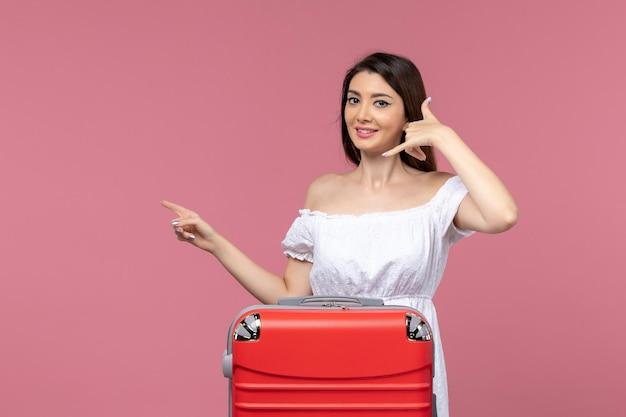Vooraanzicht jonge vrouw voorbereiding op vakantie en lachend op roze achtergrond reis in het buitenland reizen zeereis reis