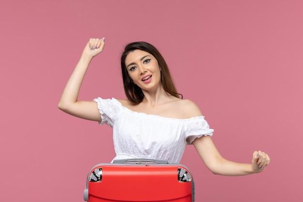 Vooraanzicht jonge vrouw voorbereiding op vakantie en opgewonden gevoel op roze achtergrond in het buitenland zeereis reis reis reis
