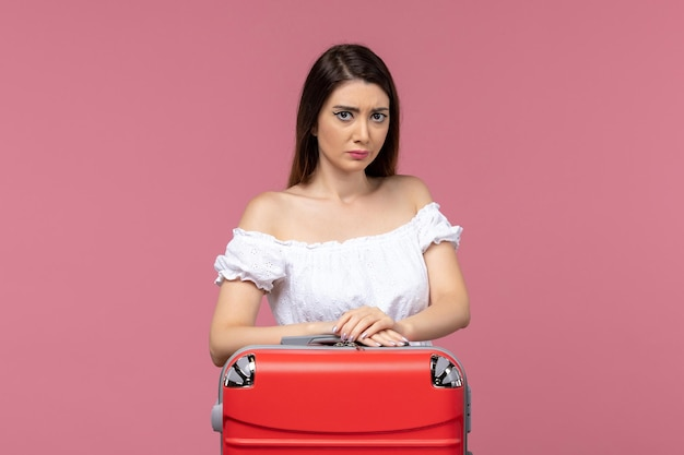 Vooraanzicht jonge vrouw voorbereiding op vakantie en verdrietig op roze achtergrond reis reizen reis vakantie vrouw in het buitenland