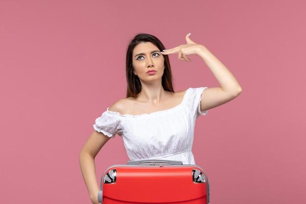 Vooraanzicht jonge vrouw voorbereiding op vakantie op de roze achtergrond reis reis reis vakantie vrouw in het buitenland