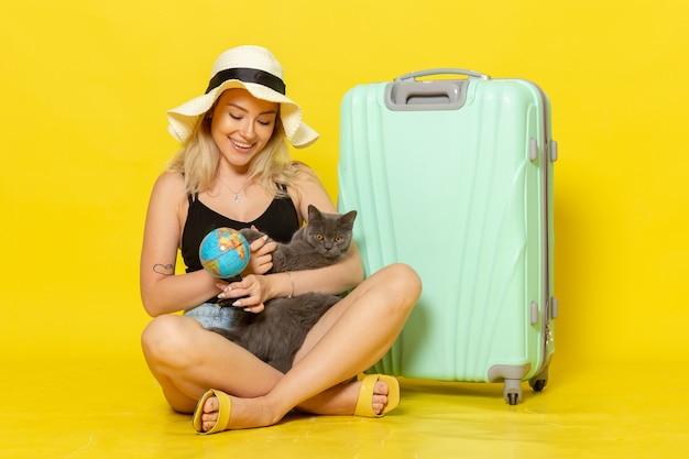 Vooraanzicht jonge vrouw zit met haar groene tas knuffelen kitten op gele muur reis vakantie zee reis zon