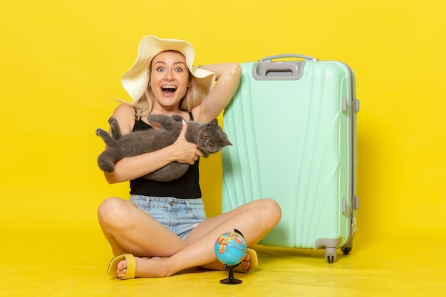 Vooraanzicht jonge vrouw zitten met haar groene tas met kitten op gele bureau reis vakantie reis zee kleur reis zon