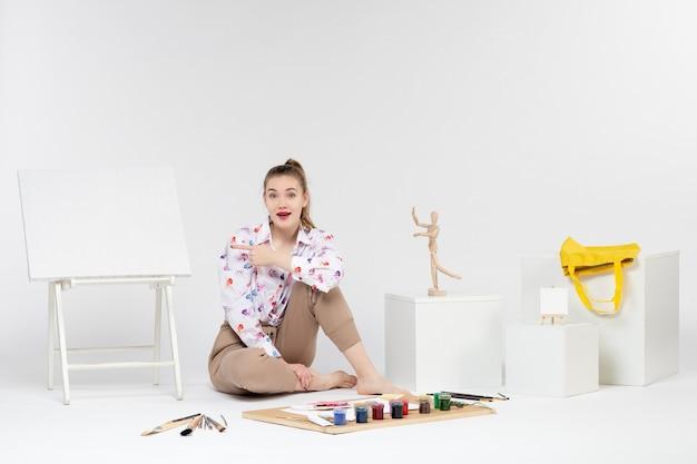 Vooraanzicht jonge vrouw zitten met verf ezel en penselen op witte achtergrond