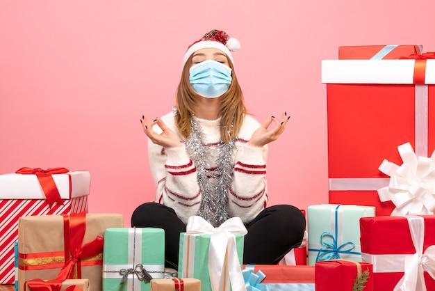 Vooraanzicht jonge vrouw zitten rond cadeautjes en mediteren