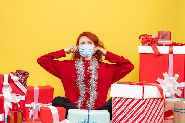 Vooraanzicht jonge vrouw zitten rond kerst presenteert met masker op geel nieuwjaar emotie covid-kleur virus