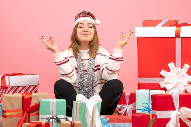 Vooraanzicht jonge vrouw zitten rond kerstcadeautjes en mediteren