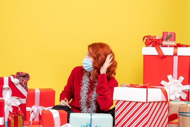 Vooraanzicht jonge vrouw zitten rond kerstcadeautjes in masker op geel