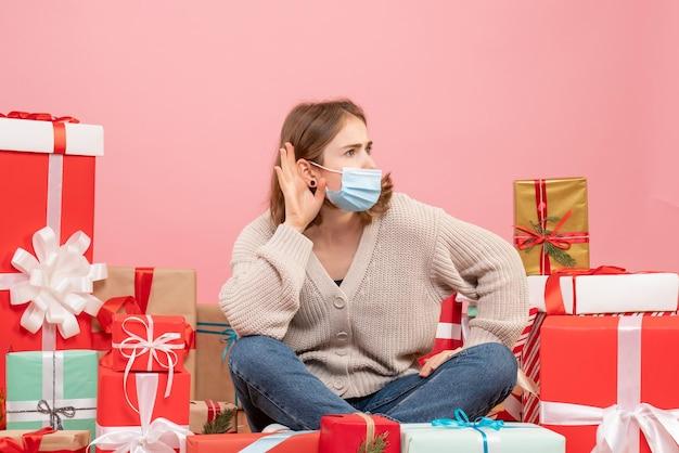 Vooraanzicht jonge vrouw zitten rond kerstcadeautjes in masker Gratis Foto