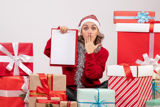 Vooraanzicht jonge vrouw zitten rond kerstcadeautjes met opmerking