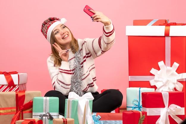 Vooraanzicht jonge vrouw zitten rond presenteert selfie te nemen