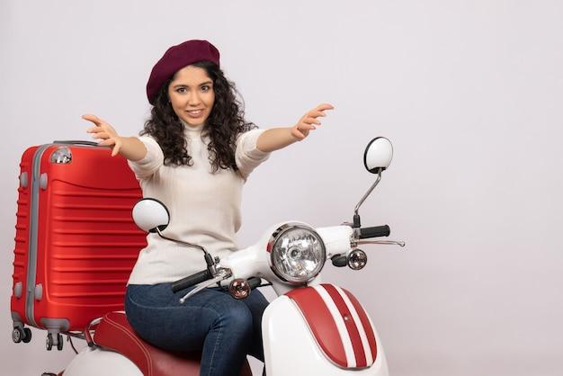 Vooraanzicht jonge vrouw zittend op de fiets op witte achtergrond stad vrouw voertuig snelheid motorfiets weg kleur vakantie