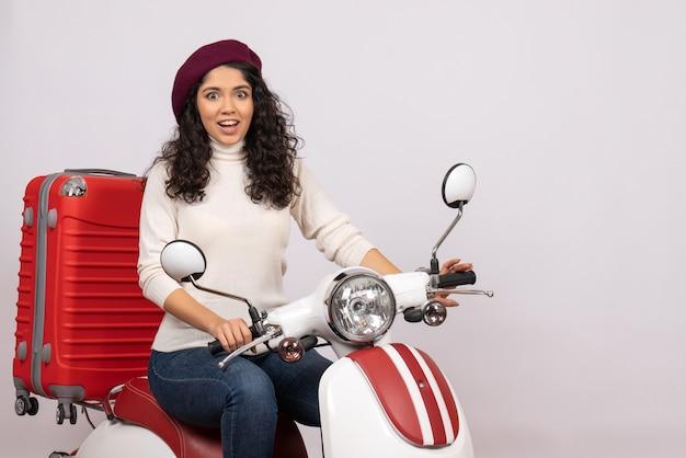Vooraanzicht jonge vrouw zittend op de fiets op witte achtergrond voertuig snelheid motorfiets weg vrouw stad kleur