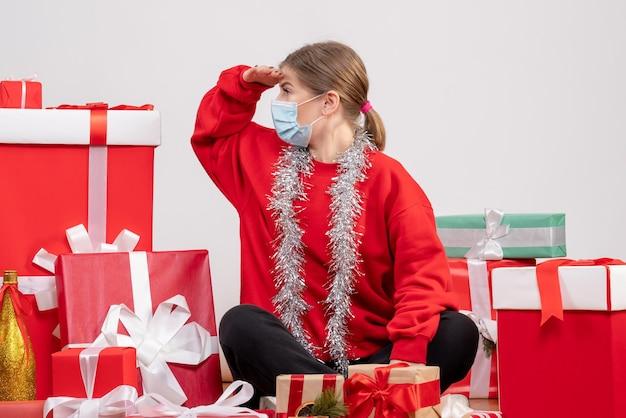 Vooraanzicht jonge vrouw zittend rond kerstcadeautjes in masker