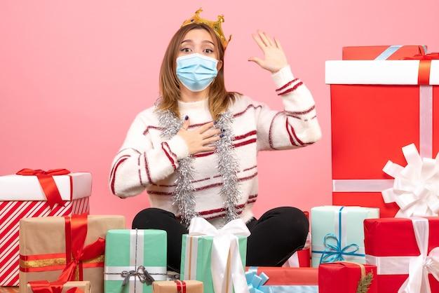 Vooraanzicht jonge vrouw zittend rond kerstcadeautjes in steriel masker