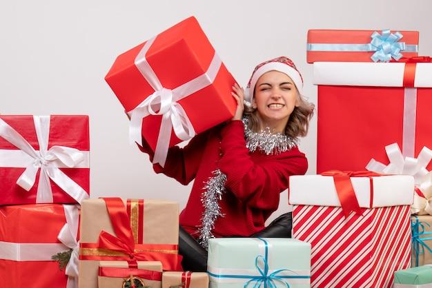 Vooraanzicht jonge vrouw zittend rond kerstcadeautjes