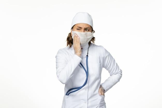 Vooraanzicht jonge vrouwelijke arts die beschermend steriel masker draagt wegens coronavirus op wit bureau