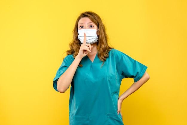 Vooraanzicht jonge vrouwelijke arts die vraagt stil te zijn op gele ruimte