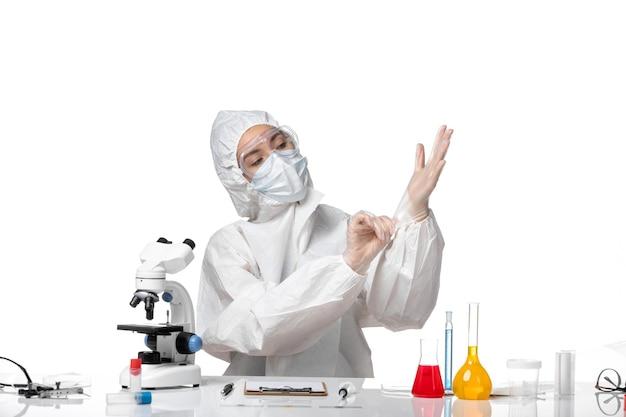 Vooraanzicht jonge vrouwelijke arts in beschermend pak met masker vanwege covid die handschoenen draagt op een witte achtergrond pandemisch covid-virus coronavirus