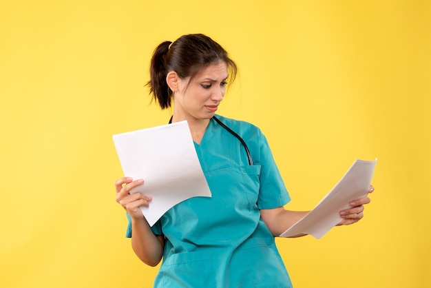 Vooraanzicht jonge vrouwelijke arts in medisch overhemd met documenten op gele achtergrond