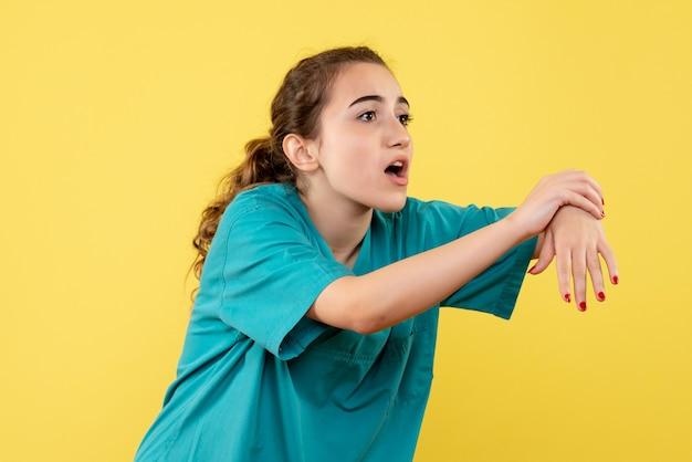 Vooraanzicht jonge vrouwelijke arts in medisch pak met gekwetste hand op gele achtergrond