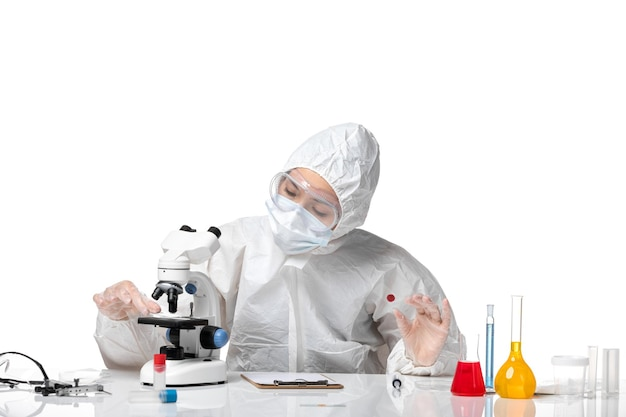 Vooraanzicht jonge vrouwelijke arts in wit beschermend pak met masker vanwege covid bezig met lichte witte achtergrond pandemisch virus gezondheid covid-