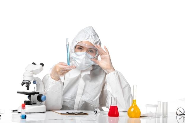 Vooraanzicht jonge vrouwelijke arts in wit beschermend pak met masker vanwege covid met blauwe oplossing op witte achtergrond splash virus pandemie covid