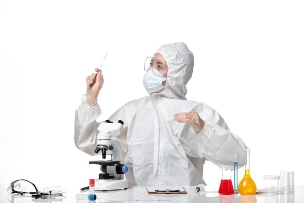 Vooraanzicht jonge vrouwelijke arts in wit beschermend pak met masker vanwege covid werken met oplossingen op lichte witte achtergrond pandemic splash virus covid-